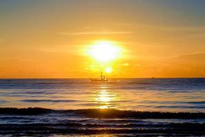 zonsondergang over de zee in de avond, boot die op zee vaart foto