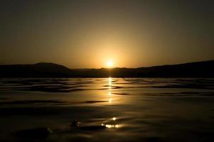 uitzicht op een meer met het zonlicht weerkaatst op het wateroppervlak foto