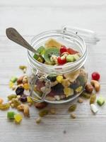 glazen pot met verschillende soorten gedroogd fruit en noten foto