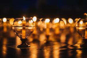 kaarsen in glas op de vloer ingericht voor gebedsceremonie in de kerk foto