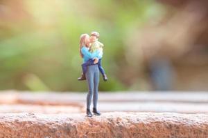 miniatuurmensen, moeder die haar schattige baby houdt, het concept van de gelukkige moederdag foto