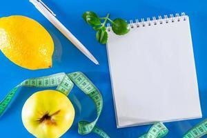 blanco notebook, fruit en meetlint op een blauwe achtergrond foto