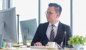knappe charmante en zelfverzekerde zakenman die in een modern kantoor werkt foto