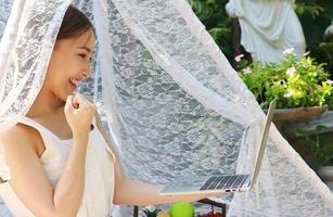 Aziatische vrouw werkt thuis met laptop tijdens covid-19 uitbraak foto