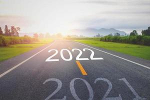 concept nieuwjaar met het woord 2021 tot 2022 geschreven op de asfaltweg foto