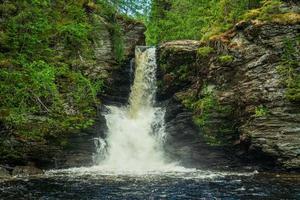 kleine waterval die langs een leistenen rotswand loopt foto