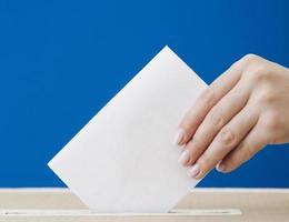 zijwaartse hand toont verkiezingsmodel op blauwe achtergrond foto