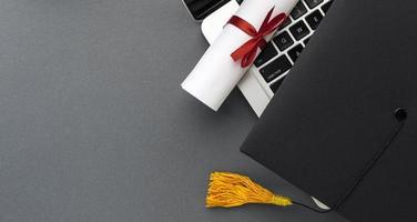 bovenaanzicht laptop met diploma en academische pet foto