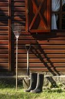 laarzen, schop en hark leunend tegen een huis foto