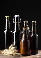 vier flessen bier op zwarte achtergrond foto