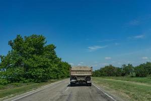 oude vrachtwagen rijdt op een gebroken asfaltweg op de achtergrond van de natuur foto