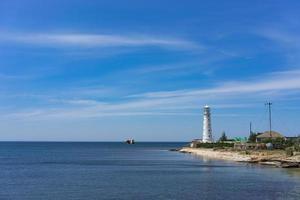 zeegezicht met mooie witte vuurtoren op blauwe hemelachtergrond. foto