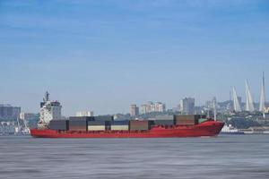 zeegezicht met een rood containerschip op de achtergrond van het stadsbeeld. foto