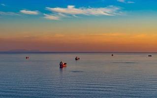 zeegezicht met tanker en schepen op de achtergrond van de zee en de kustlijn. foto