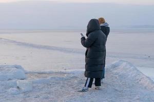 mensen in winterkleren staan op het ijskoude oppervlak van de zee. vladivostok. foto