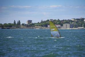 zeilboot in de zee op de achtergrond van de kustlijn foto