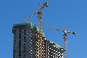 huis in aanbouw en kranen tegen de blauwe hemel. foto