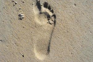 natuurlijke achtergrond van zand met de afdruk van een menselijke voet. foto