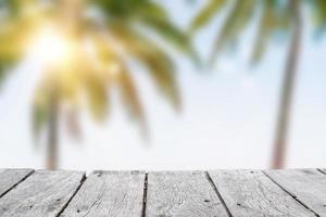 selectieve focus van oude houten tafel met een wazig mooi strand met tropische palmbomen om uw product weer te geven. foto