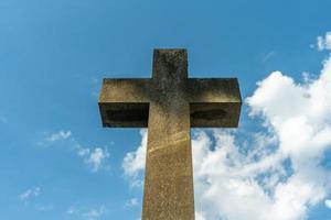 groot kruissymbool gemaakt van steen tegen een blauwe hemel foto