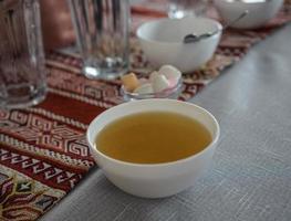 thee in een witte kom op een kleurrijk tafelkleed foto