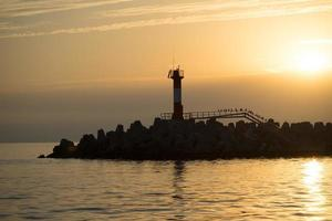 silhouet van de kustlijn tegen de zonsondergang. foto