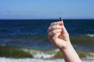 hand van het kind met zeeglas op de achtergrond van de zee. foto
