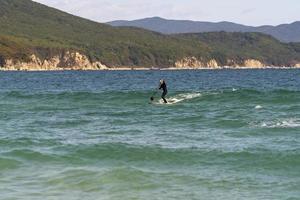 zeegezicht met een sap-surfer op een bord. primorsky krai foto