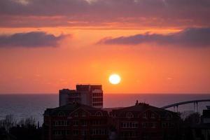 landschap met uitzicht op de zonsondergang over zee en stad foto