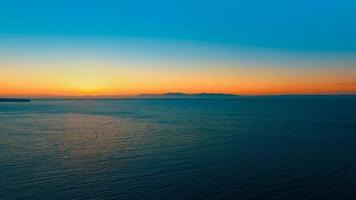 zeegezicht met oranje zonsondergang over de horizon. foto