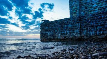 stenen muur met een pistool op de achtergrond van het zee-landschap. foto