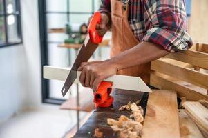 professionele timmerman man aan het werk met houtwerk industrie tool, ambachtsman persoon workshop met hout en apparatuur houtwerk constructie foto