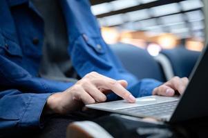 zakenman zit en gebruikt een laptop om op de luchthaven te werken, jongere die reist, reist en internetcommunicatietechnologie heeft voor werk wanneer hij binnen wacht op een luchthaven voor vertrek foto