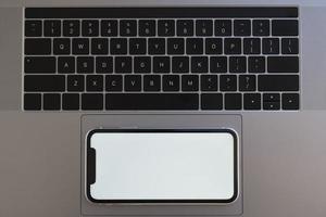 bovenaanzicht telefoon op laptop touchpad foto