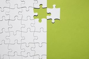 wit puzzelstukje apart met wit puzzelraster op groene achtergrond foto