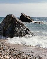 golven en grote rotsen op het strand foto