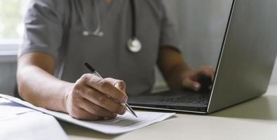 zijaanzicht arts met een stethoscoop die op laptop schrijfpapier werkt foto