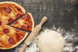 gekookte pizza en deeg foto