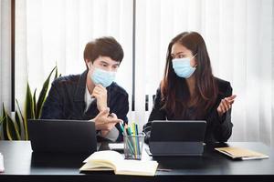 twee jonge bedrijfsleiders in een vergadering met maskers op foto