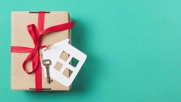 bruine geschenkdoos gebonden met rood lint huissleutel turkoois oppervlak. mooi fotoconcept van hoge kwaliteit en resolutie foto