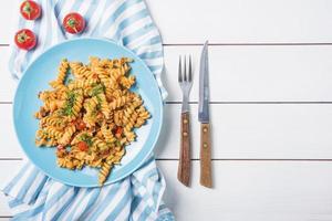 pasta fusilli met tomatenbestek witte houten tafel. mooi fotoconcept van hoge kwaliteit en resolutie foto