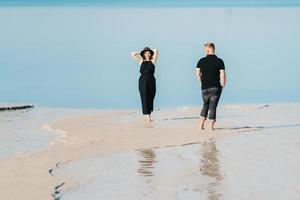jong stel een man met een meisje in zwarte kleren lopen op het witte zand foto