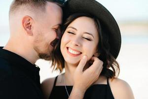 jong koppel een jongen en een meisje met vrolijke emoties in zwarte kleding lopen door de witte woestijn foto