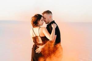 jongen en een meisje in zwarte kleren knuffelen en rennen op het witte zand foto