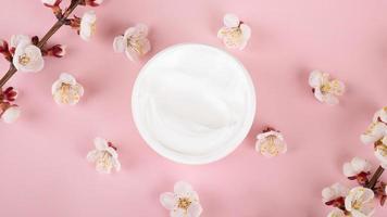 crème en bloemen op roze achtergrond, cosmetische schoonheidshuidverzorging foto