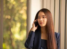 Aziatische zaken vrouw met behulp van mobiele telefoon in een kantoor foto