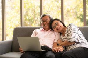 senior aziatische man en vrouw ontspannen op vakantie in de natuurlijke woonkamer achtergrond met moderne technologie foto