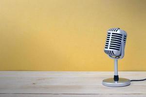 vintage microfoon geïsoleerd op houten en gele achtergrond foto