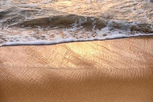 glanzende tropische overzeese golf met bel op bruin strand bij zonsondergang foto