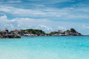tropische zee met rotsen stapel en blauwe hemel foto